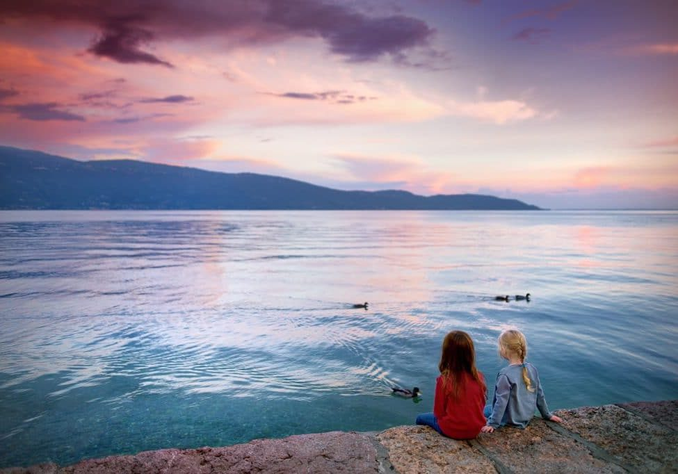 Two little girls enjoying beautiful sunset in Gargnano, a small town and comune in the province of Brescia, in Lombardy. It is situated on the western shore of Lake Garda.